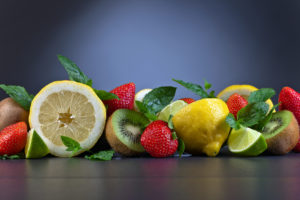 The ripe juicy fruits and peppermint leaves on a dark background