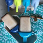 Two Caribbean-Spiced Ice Lollies and fresh spices used to make them sitting in front of four more