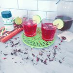 Two glasses of sugar-free Hibiscus Lime Iced Tea surrounded by dried hibiscus petals