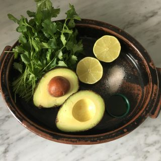 Dish filled with avocado, lime, cilantro, salt, and maple syrup for making a simple low FODMAP salad dressing recipe