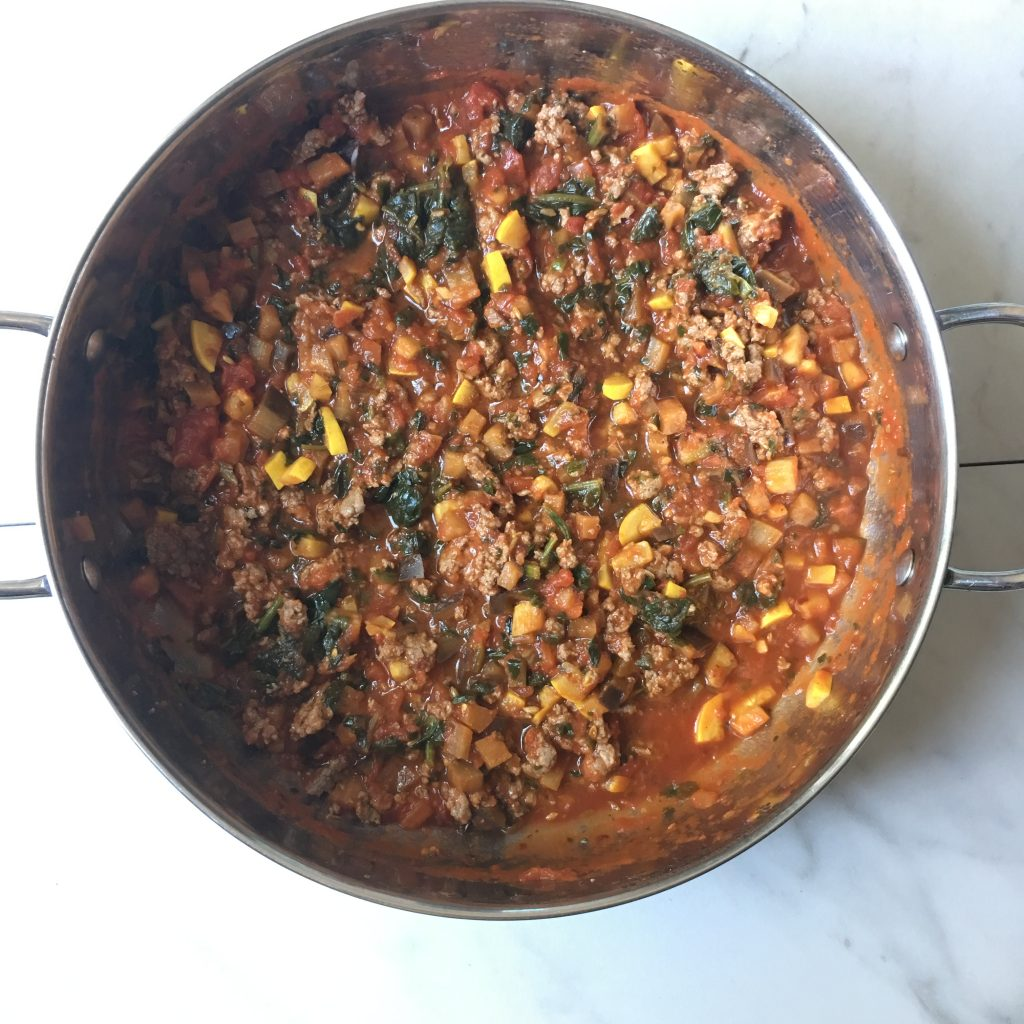 Pan of cooked ground beef, zucchini, eggplant, and spinach in marinara sauce