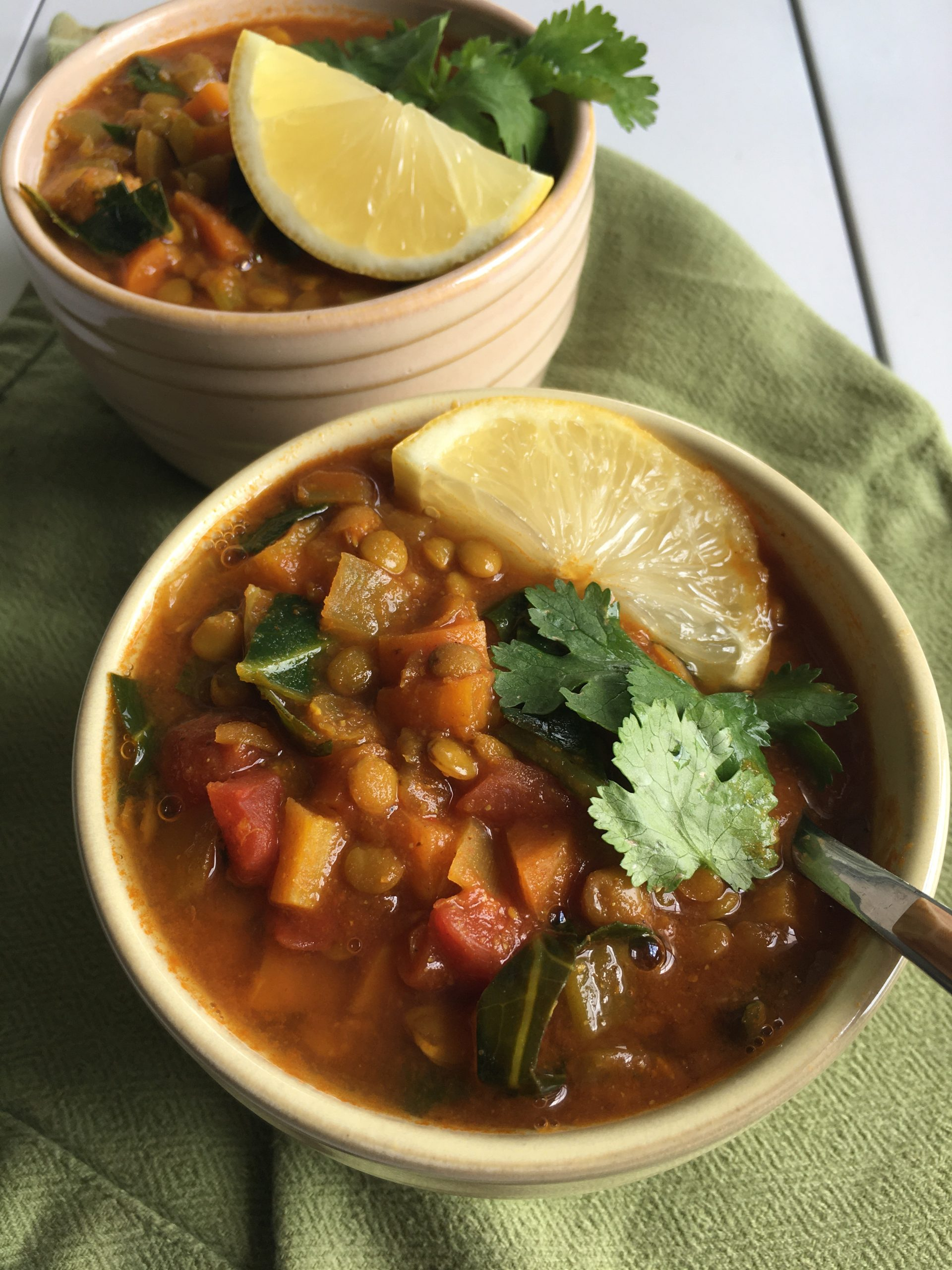 Two bowls of spiced vegetable lentil soup topped with cilantro and lemon wedges